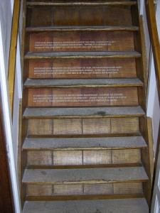 Lettering on the stairs: EXCELSIOR, ONCE AGAIN! A COMPANION - LADDER THIS TIME, LEADING TO A LOFT. / PERHAPS 100,000 HAVE CLIMBED THESE STAIRS - BEFORE YOU, AND BEFORE / GOING UP THIS LINE. HERE YOUR ARE ON HOLIER GROUND THAN ANY.