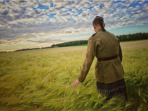 A Scottish soldier passes through a field of wheat.