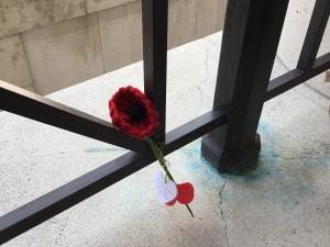 Woolen poppy upon the Menin Gate Memorial.